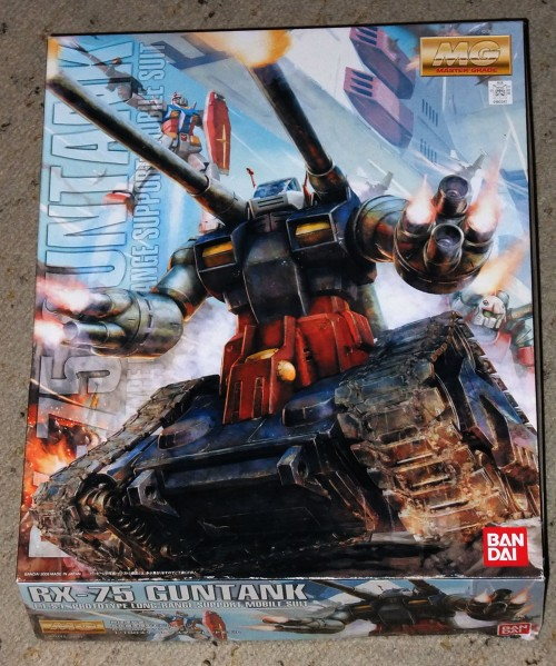 """Sure, it might be as practical as the proverbial """"screen door on a space shuttle"""", but the boxtop illustration of the RX-75 makes this bad idea seem bad-assed! Kudos to Bandai's art department for making the Guntank look killer, instead of cannon-fodder!"""